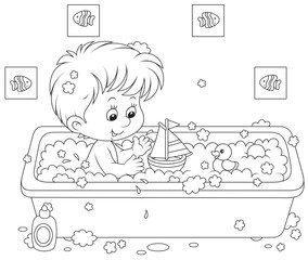 Little boy playing with toys in a bath with foam