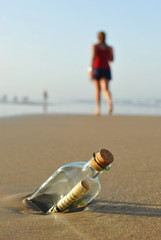 Message in a bottle on the beach, woman walking