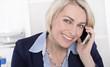 Portrait einer lachenden älteren Geschäftsfrau mit Smartphone