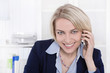 Lachende ältere Business Frau mit Mobiltelefon im Büro