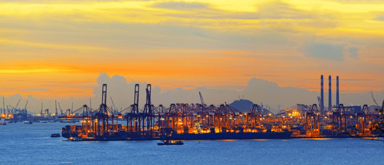 Silhouette of several cranes in a harbor, shot during sunset.