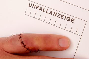 Mann mit genähtem Finger erstellt Unfallanzeige