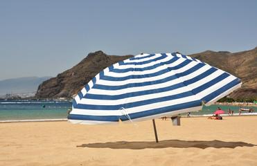 Striped umbrella on the Teresitas beach of Tenerife island. Cana