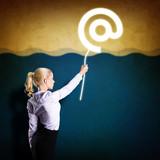 junge Frau hält E-Mail Symbol fest