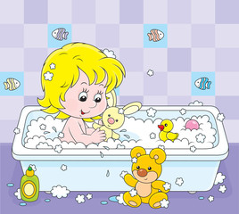 Little girl playing with toys in a bath with foam