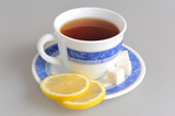A cup of lemon tea and two slices of lemon, refined sugar on sau