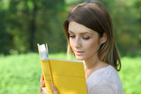 Blonde girl reading a book in the park