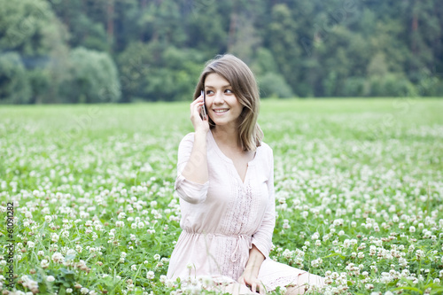 Young woman sitting on a green lawn - 61091282