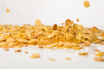 Cornflakes falling into a pile, over white background