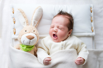 Cute yawning baby girl in а crib with a toy rabbit