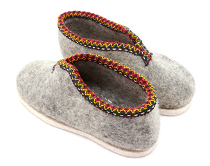 Two traditional grey felt slippers posed heel to toe
