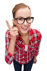 smiling teenager in eyeglasses with finger up