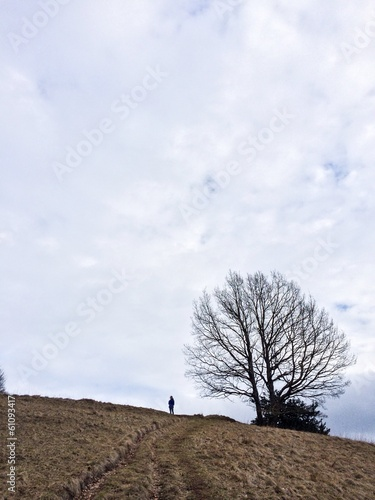 Girl standing alone next to a tree