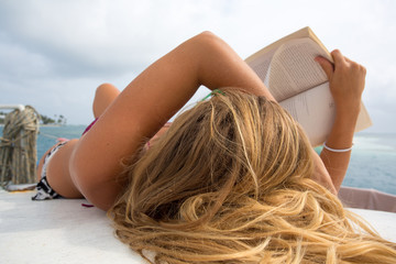 Young woman is relaxing and sunbathing while reading a book