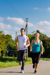 Sportliches Paar beim Joggen auf dem Land