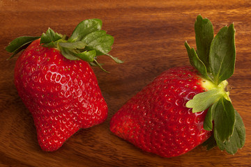 Two strawberries on wood,