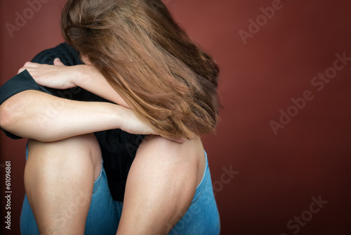 Sad and lonely young woman crying