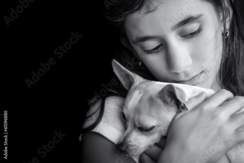 Motional portrait of a sad lonely girl hugging her small dog