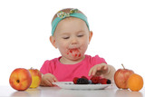 Little girl eating berry fruits.
