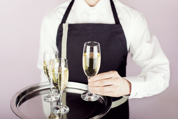 Waiter carrying a tray with champagne