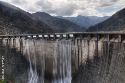 Poster Dam dam with overflow under cloudy sky