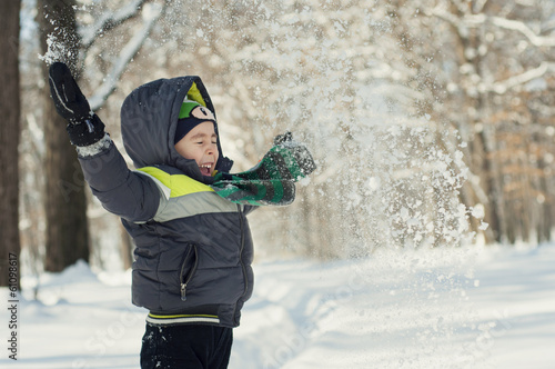 Portrait of funny child in winter playing with snow and laughing