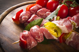 skewers of chicken and sausage on the chopping board