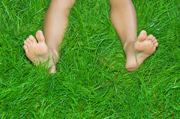 Female  legs are in a green grass