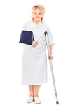 Female patient with broken arm standing with a crutch