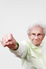 Angry senior woman punching the air.