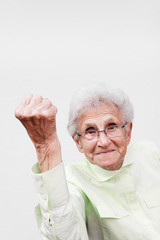 Angry senior woman punching the air.