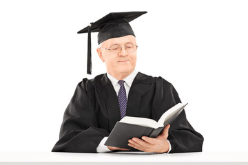Mature man with graduation hat reading book seated on table
