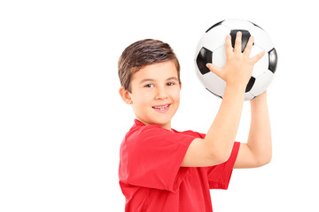 Young boy holding a soccer ball and looking at camera
