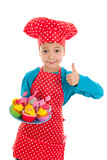 Studio portrait boy as little cook with cupcakes