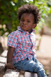 Outdoor portrait of a black baby sited on a bench