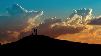 People silhouettes on sunset sky background.