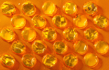 Orange package of pills tablets drug medicine as background