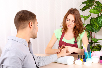Beautiful girl manicurist doing manicure for man in beauty