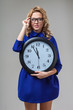 woman wearing eyeglasses holding big clock