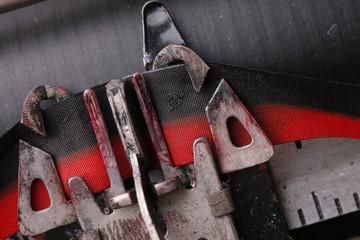 Macro close up of a typewriter key striking the ink ribbon