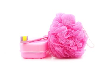 pink toothbrush, soapboxand shower scrubber on white background