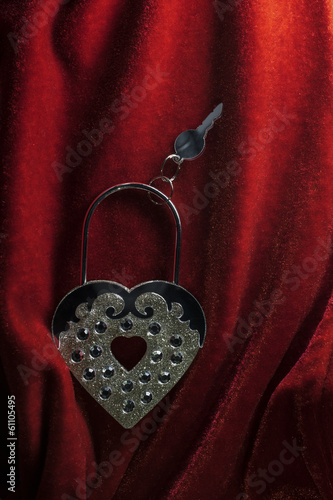 Silver love lock with a key on red velvet