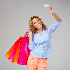 woman holding blank card and bags