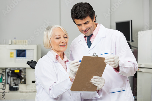 Technicians Writing On Clipboard In Laboratory