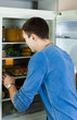 man searching for something in refrigerator