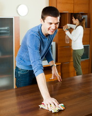 Man with wife dusting furniture
