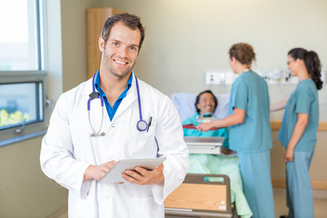 Doctor Using Tablet Computer While Nurses Serving Breakfast To P