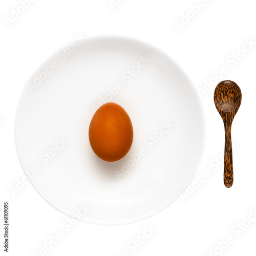 Brown egg on a white plate and wooden spoon isolated on white