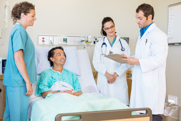 Doctors Discussing Notes While Nurse And Patient Looking At Them