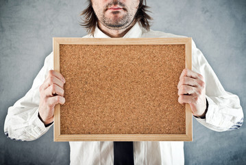 Businessman holding blank bulletin board